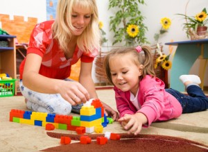 Nanny and child are playing with bricks